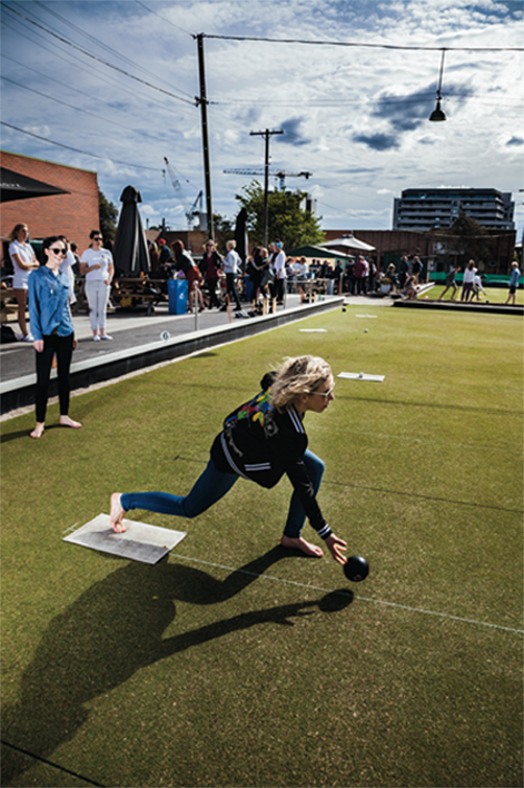 girl playing lawn bowls