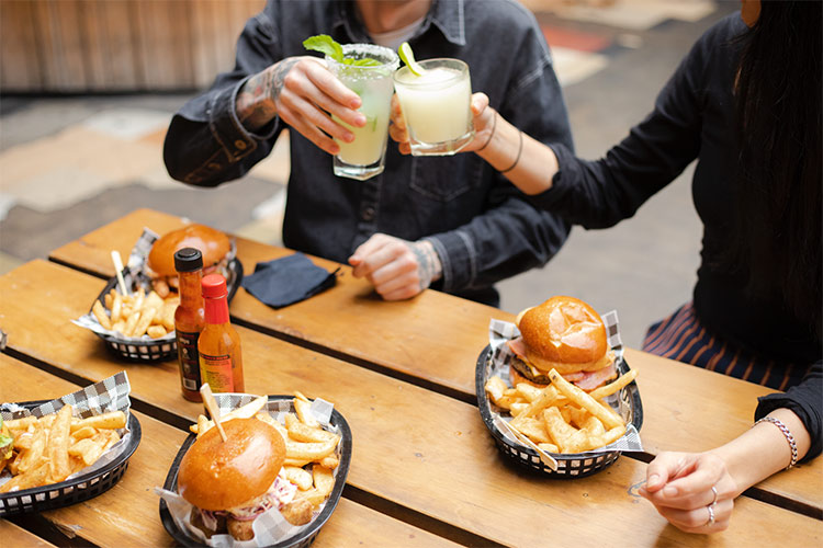 two people sitting at a bench with burgers and fries in front of them and cocktails in hand