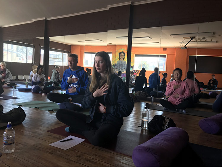 People sitting down and meditating in the Summer Healing Yoga Studio