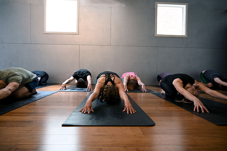 a group of people stretching in a yoga studio in brunswick