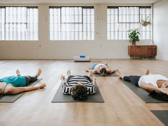women lying down practicing yoga in a studio in Brunswick