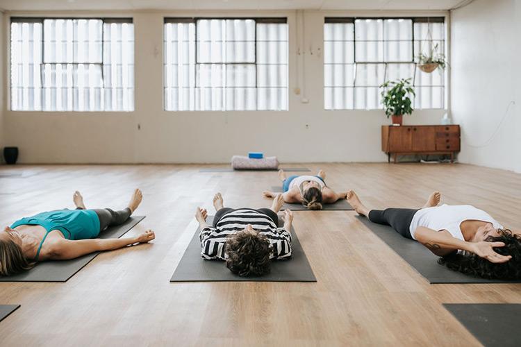 women lying down practicing yoga in a studio in Brunswick