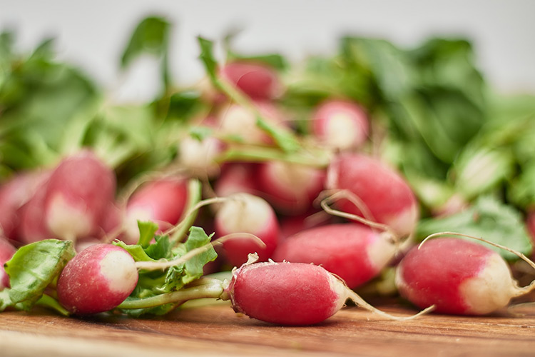 a pile of radishes sitting on a chopping board