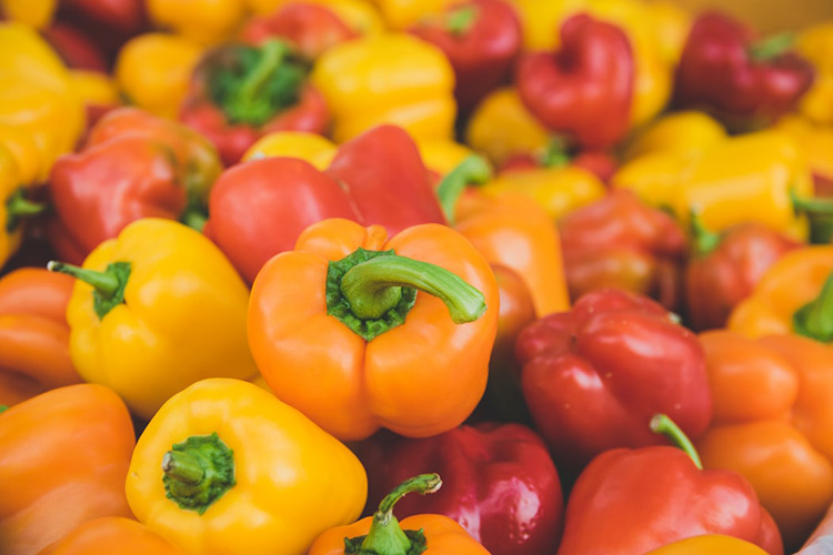 red, yellow and red capsicums sitting in a bunch together